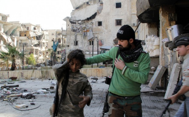 Syrian youth Ahmed, 13-years old (L) and Faris (R), 16-years old, who allegedly fight alongside opposition fighters from the Sadeq Al-Amin Brigade, get prepared with another member of the brigade before a patrol in the Salah al-Din neighbourhood of the northern Syrian city of Aleppo on November 17, 2013. For three weeks, the army has been pressing a campaign to retake rebel-held areas in Aleppo, particularly east of the country's second city, and jihadist fighters have called for mass mobilisation to counter regime advances. AFP PHOTO / KARAM AL-MASRI (Photo credit should read KARAM AL-MASRI/AFP/Getty Images)